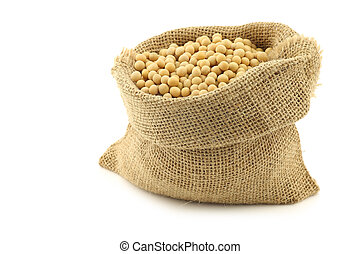 soy beans in a burlap bag on a white background