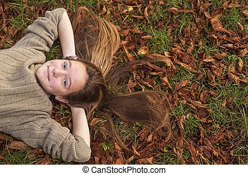 ?ute girl lying on fallen leaves in autumn park.
