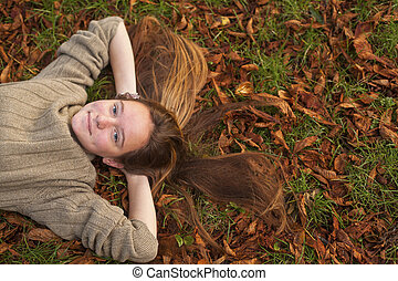 Young pretty girl lying on the ground with fallen leaves in autumn park.