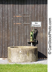 Well with a hand pump - A well in front of a barn with an...