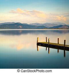Wooden pier or jetty and on a blue lake sunset and sky...