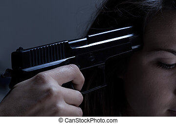 Close-up of woman holding gun and going to commit suicide