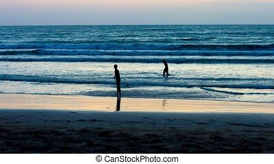 Children play with a ball near the tropical sea at sunset
