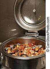 Chafing dish heater filled with ready food inside.