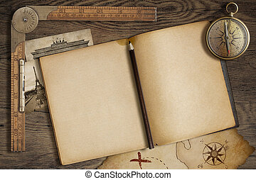Open blank diary with map, pencil and compass. Adventure and...