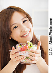 beautiful asian young woman eating salad
