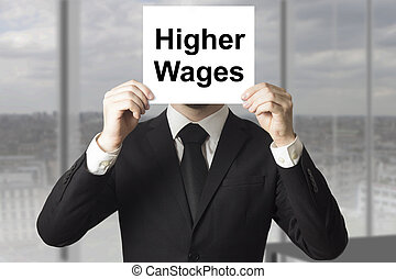 businessman hiding face behind sign higher wages -...