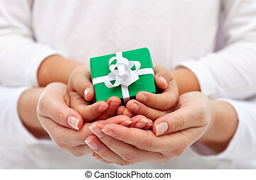 Giving a present - child and woman hands with gift box -...