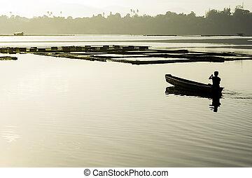 Early Lake Fishing - Man paddles towards his lake fishpens...