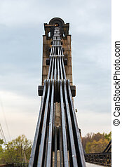 old rusty steel suspension bridge of forged elements....