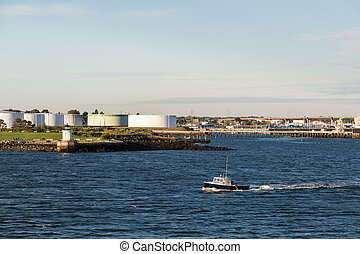 Trawler Past Fuel Tanks - Small fishing trawler past old...