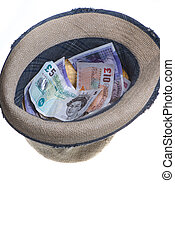 straw hat filled up with cash isolated on white