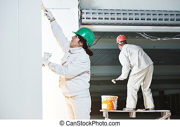 Plasterers at indoor wall work - plasterer and painter at...