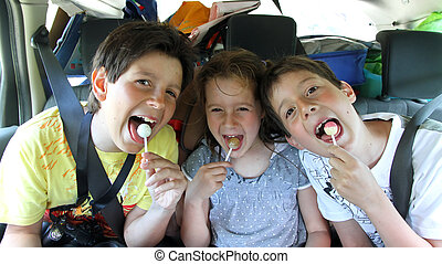 three happy brothers while traveling by car eating a candy -...