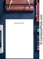 sheet of paper on a table with the word new project. Insert...