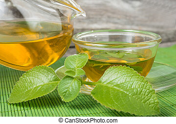 Pouring tea into cup of tea on green bamboo mat