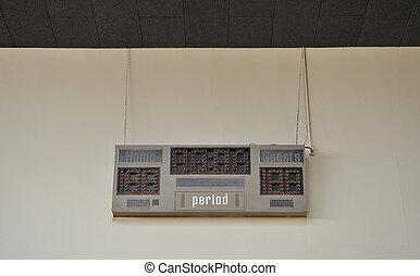 Scoreboard - A blank scoreboard against a tan wall in an...