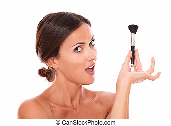 Young woman with make up brush looking at camera