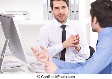 two businessmen having discussion in office over shoulder...