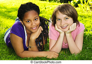 Girl friends - Two happy teenage girls laying on grass