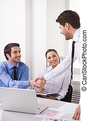 Side view of three people working on computer at office. Businesspeople sitting at desk in office and shaking hands
