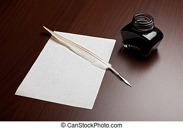 Quill, ink and paper - Ink, quill and an empty page on brown...