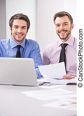 Two business men working together on laptop in office. Two happy business men smiling at camera