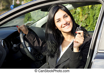 Happy smiling woman inside car showing keys - Cute young...