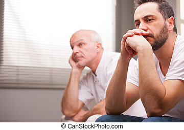 men concerned about something in a living room - a couple of...