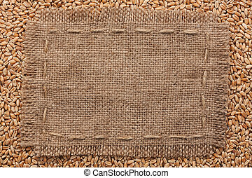Frame of burlap lying on a wheat background, with place for...