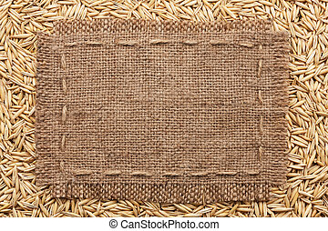 Frame of burlap lying on a oats background, with place for...