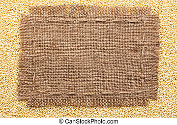 Frame of burlap lying on a millet background, with place for...