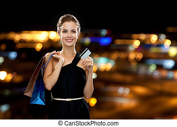 smiling woman with shopping bags and credit card - shopping,...