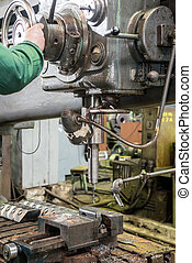 machinist working on industrial drilling machine in workshop