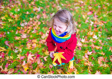 Little girl in autumn park - Funny laughing little girl in a...