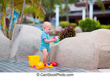 Baby at pool side - Cute little baby boy playing with...