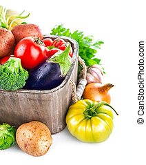 Fresh vegetables in wooden bucket with greens. Isolated on...