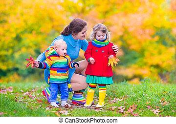 Mother and children in an autumn park - Young happy mother...