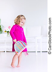 Little girl sweeping the floor - Funny curly little girl in...