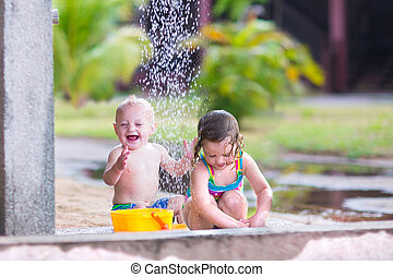 Kids in an outdoor shower - Two happy children, adorable...