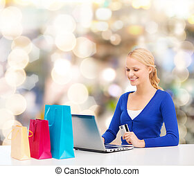 smiling woman with credit card and laptop - christmas,...