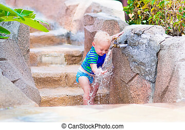 Baby boy playing with water tap outdoors - Adorable blond...