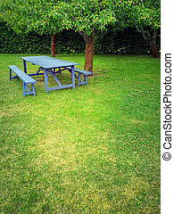 Wooden table in summer garden with green lawn