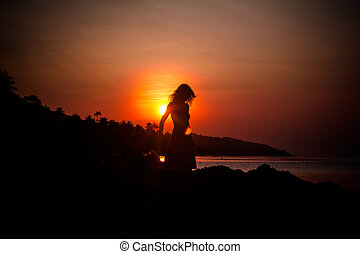girl silhouette on sunset beach background