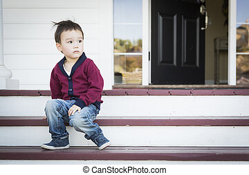 Melancholy Mixed Race Boy Sitting on Front Porch Steps -...
