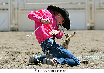 Goat Tying - Young cowgirl tying a goats legs in a rodeo...