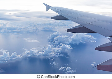 Aircraft wing on the clouds, flying evening background -...