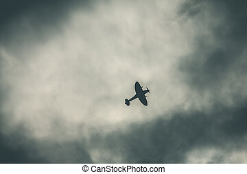 Fighter plane on cloudy sky - Old fighter plane on dark...