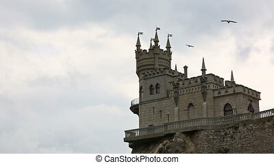 Birds fly over castle Swallows Nest in Yalta, the Crimea