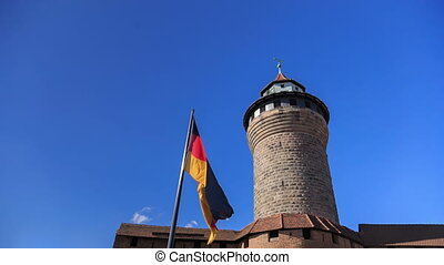 Nuremberg Castle Sinwell tower with blue sky and german flag...